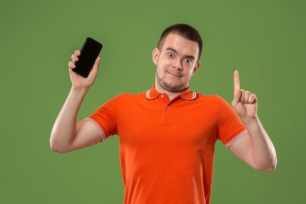 O homem feliz que mostra na tela vazia do telefone móvel contra a parede verde.