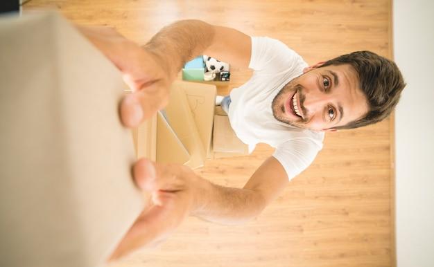 O homem feliz segura uma caixa de papelão e olha para a câmera. vista de cima