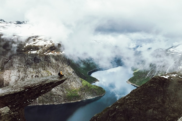 O homem fica no final de trolltunga antes das montanhas