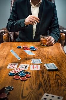 O homem, fichas para jogar, beber e jogar cartas