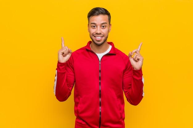 O homem filipino novo da aptidão indica com ambos os dedos dianteiros acima de mostrar um espaço vazio.