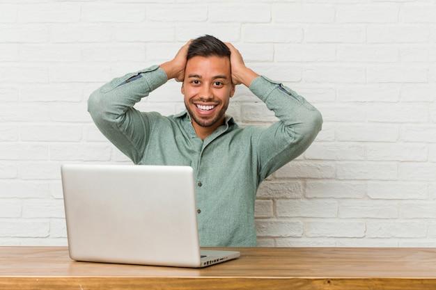 O homem filipino novo que senta o trabalho com seu portátil ri alegremente mantendo as mãos na cabeça.