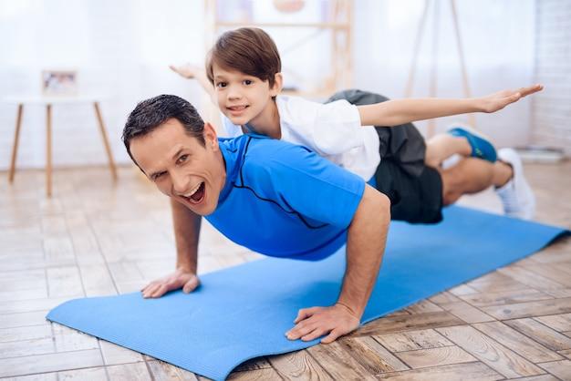 O homem flexionado do chão com o menino nas costas.