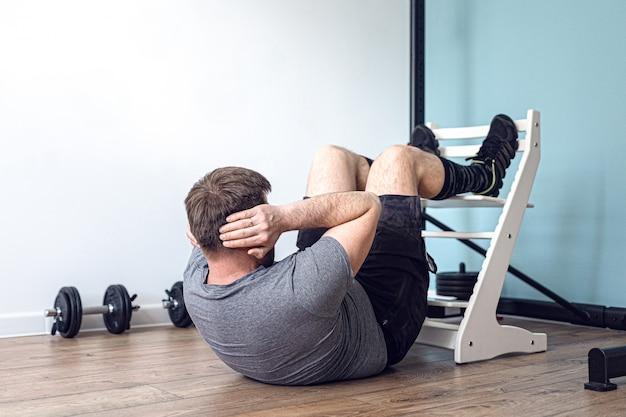 O homem forte e atlético de camiseta e shorts está fazendo abdominais