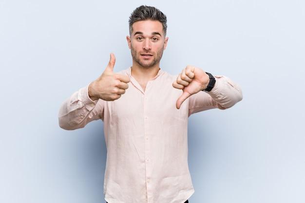 O homem fresco considerável novo que mostra os polegares acima e os polegares para baixo, difícil escolhe o conceito