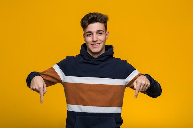 O homem fresco novo que veste um hoodie aponta para baixo com dedos, sentimento positivo.