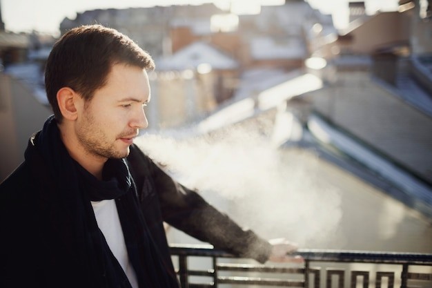 O homem fuma no telhado no dia ensolarado
