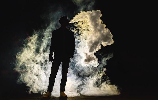 O homem fumando no fundo escuro. noite noite