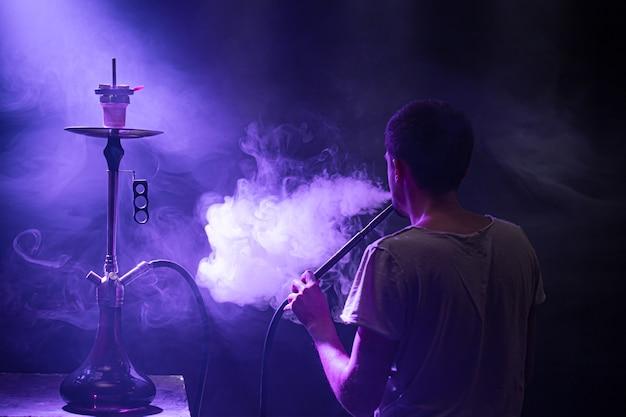 O homem fumando o clássico shisha. lindos raios coloridos de luz e fumaça. o conceito de fumar narguilé.