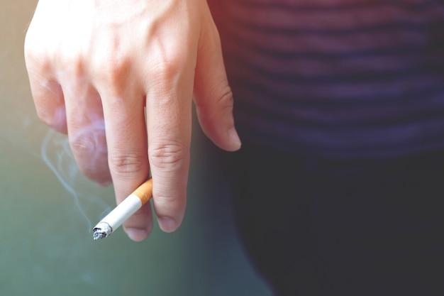O homem fumando um cigarro na mão. a fumaça do cigarro se espalhou.