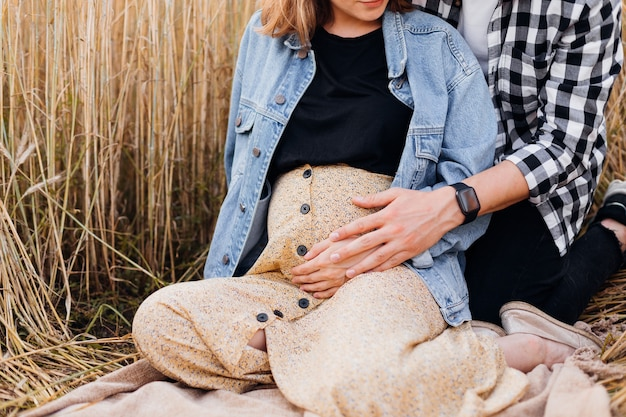 O homem gentilmente abraça a barriga da esposa grávida com a mão, ouvindo os movimentos da criança. gravidez e cuidados. felicidade e ternura. cuidado e atenção. amor e atenção.