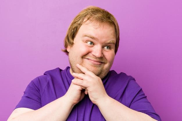 O homem gordo da ruiva autêntica nova mantem as mãos sob o queixo, olhando feliz de lado.