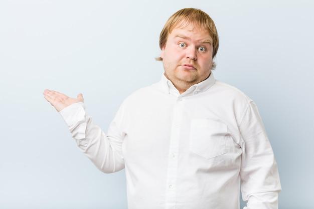 O homem gordo do ruivo autêntico novo imprimiu guardar a palma do copyspace.