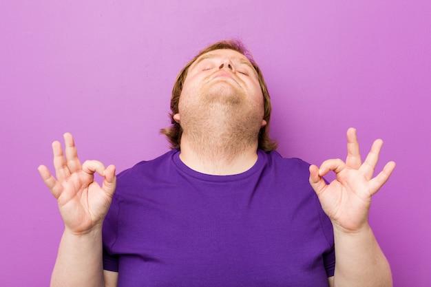 O homem gordo do ruivo autêntico novo relaxa após o dia de trabalho duro, está executando a ioga.