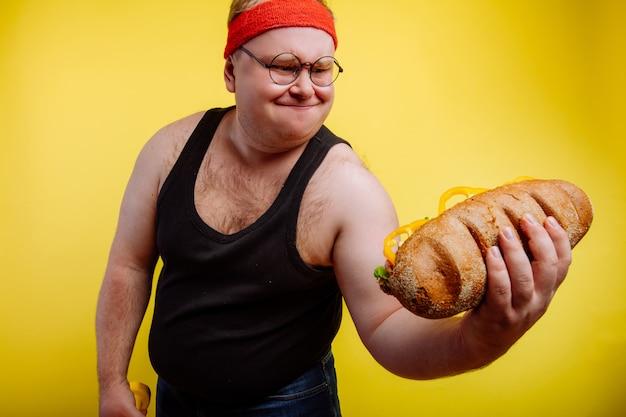 O homem gordo engraçado sua enquanto levanta o hamburguer