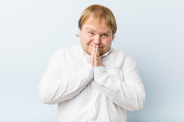 O homem gordo jovem ruiva autêntica, segurando as mãos em rezar perto da boca, sente-se confiante.