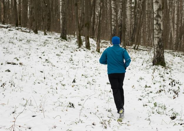 O homem gosta de correr na floresta de inverno.