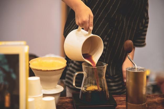 O homem goteja o café especial quente na manhã ao dia na cafetaria.