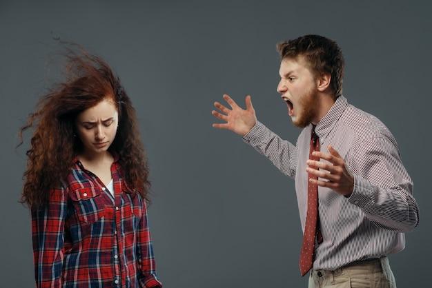 O homem grita na mulher como um vento forte soprando na cara, o conceito de emoção. homem grita, forte fluxo de ar sopra na garota, fundo preto
