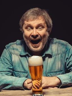O homem gritando em camisa jeans com copo de cerveja