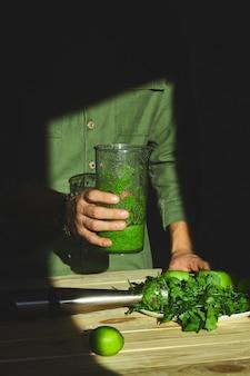 O homem guarda o batido saudável da desintoxicação, cozinhando com o misturador com frutas frescas e espinafres verdes, conceito da desintoxicação do estilo de vida. bebidas veganas.