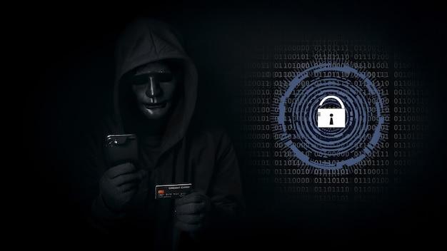 O homem hacker com capuz e máscara usa smartphone e cartão de crédito, quebra dados de segurança e hackear senha com chave desbloqueada.