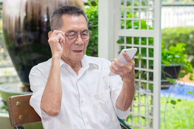 O homem idoso asiático idoso feliz guarda vidros do olho e olhando o smartphone em exterior.