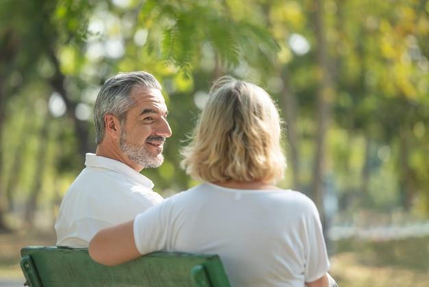 O homem idoso caucasiano olha a mulher ao sentar e relaxar em bancos no parque público. conceito de usar a vida feliz. no feriado do casal de idosos.