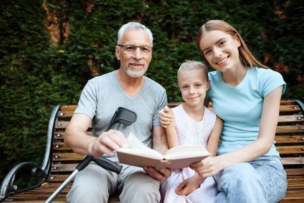 O homem idoso com seus parentes senta-se em um banco.
