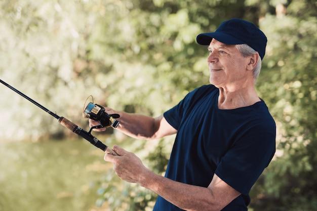 O homem idoso continua girando e vira o carretel de pesca