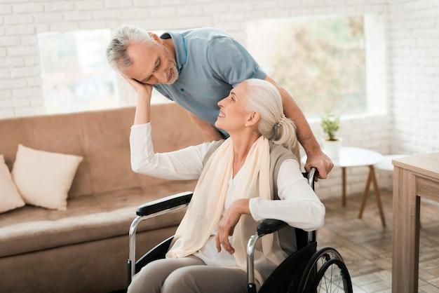 O homem idoso cuida da mulher madura em cadeira de rodas.