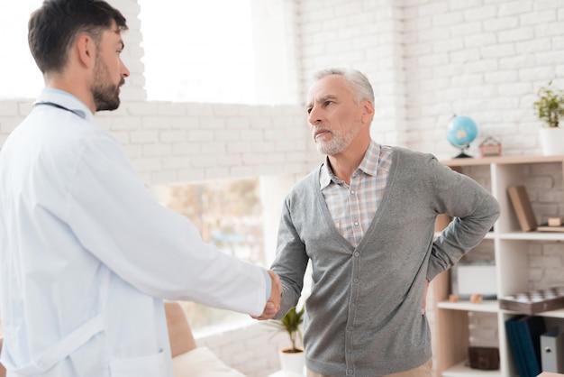O homem idoso de cabelo cinzento queixa-se da dor volta ao doutor.