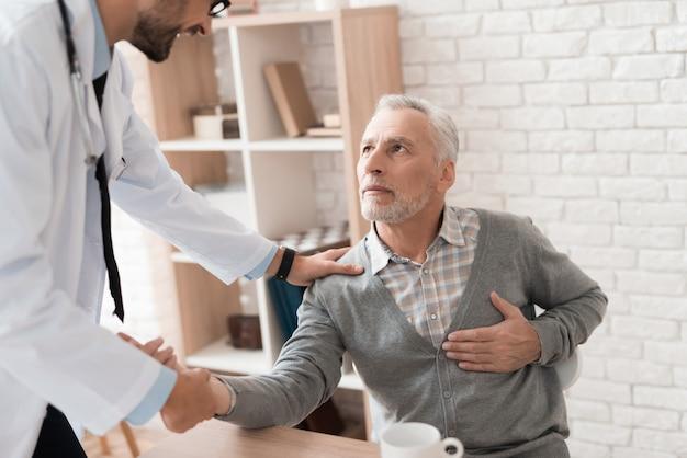 O homem idoso de cabelos cinzento queixa-se ao doutor para a dor no coração.
