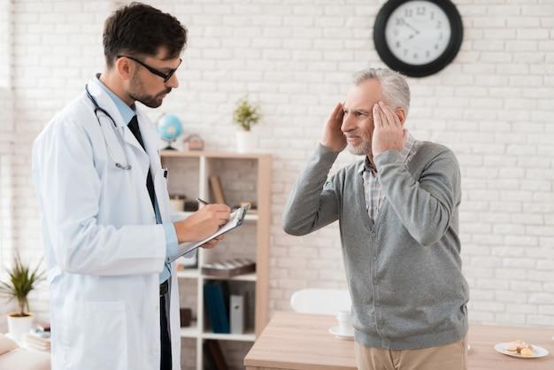 O homem idoso de cabelos cinzento queixa-se ao doutor sobre a dor na cabeça.