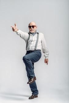 O homem idoso elegante faz os dedos parecidos com uma arma. sénior maduro, cara