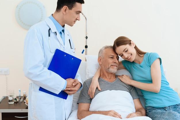O homem idoso encontra-se em uma cama. ele está passando por reabilitação.