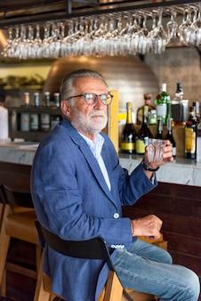 O homem idoso está sentado em um pub