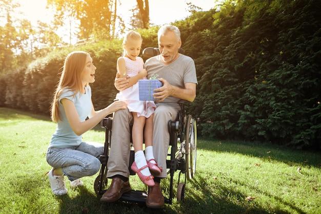 O homem idoso está sentado em uma cadeira de rodas. ele é visto por uma mulher com uma garota.