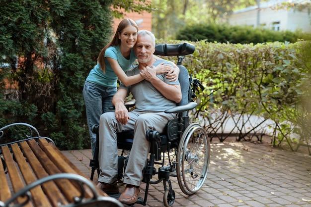 O homem idoso está sentado em uma cadeira de rodas. perto está sua filha e abraça o velho.