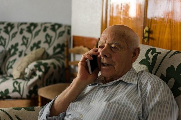 O homem idoso está usando seu smartphone em casa