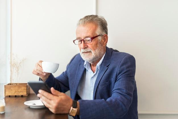 O homem idoso está usando tablet digital