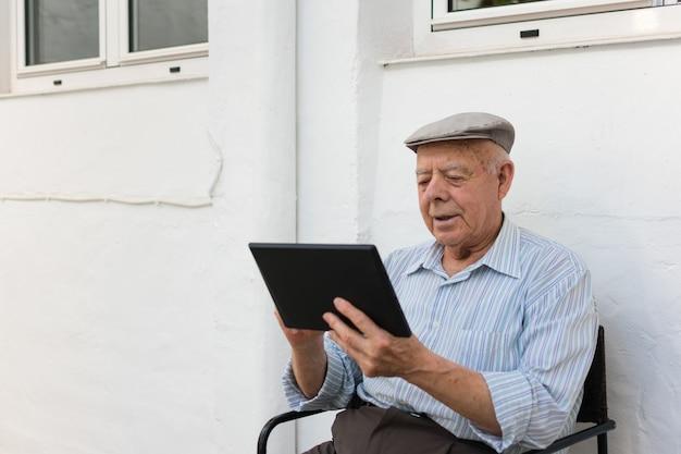 O homem idoso está usando um tablet no quintal de sua casa