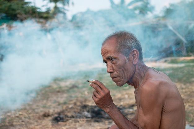 O homem idoso estava fumando um homem idoso estava fumando um cigarro durante o intervalo do trabalho