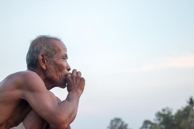 O homem idoso estava sentado fumaça