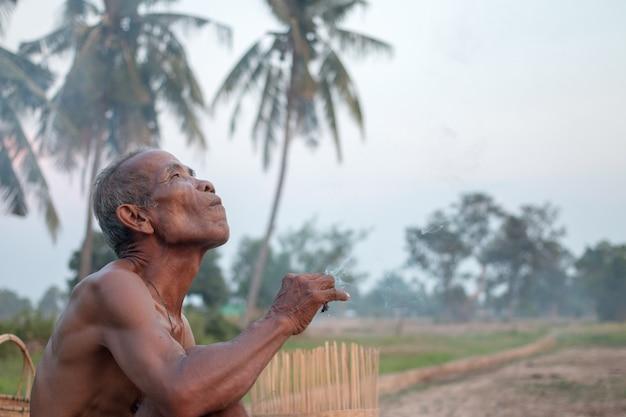 O homem idoso estava sentado fumo