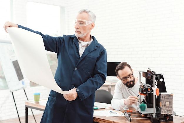 O homem idoso no primeiro plano está estudando um modelo.