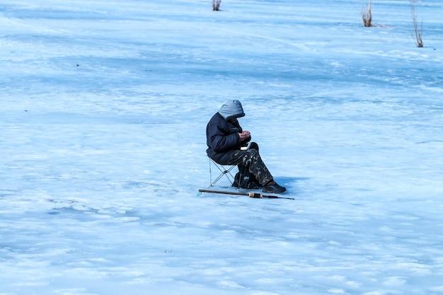 O homem idoso tem pescado no lago no inverno.