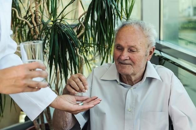 O homem idoso toma medicação