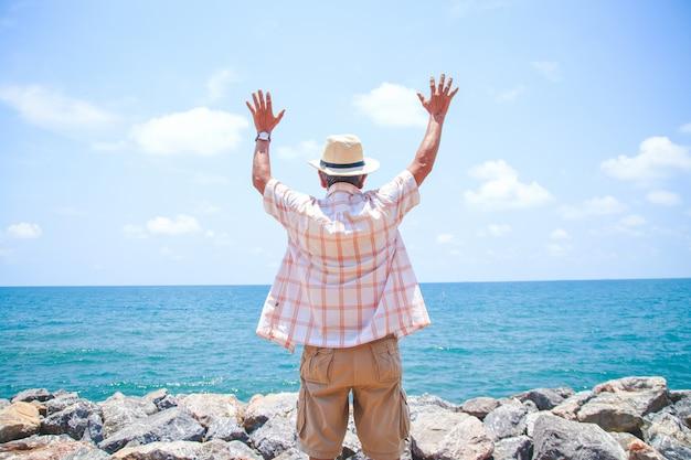 O homem idoso usava um chapéu, virou as costas, deixando-o levantar as mãos com alegria ao vir para o mar.