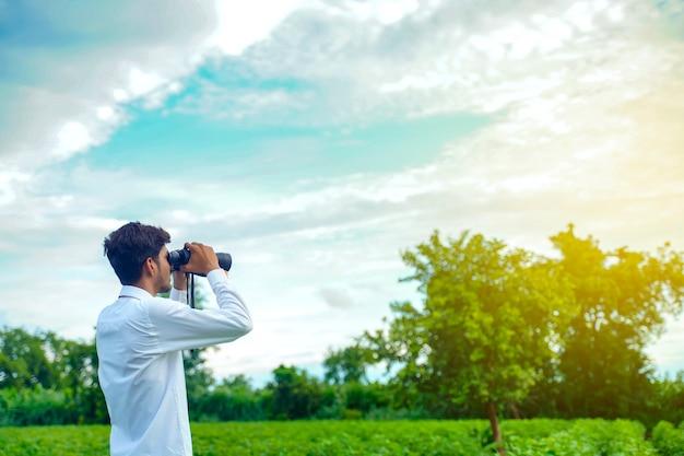 O homem indiano gosta da natureza com binóculos